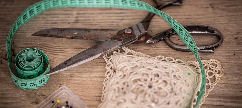 Auf dem Bild sind ein türkises Maßband, eine Schere und ein Stecknadelkissen zu sehen.