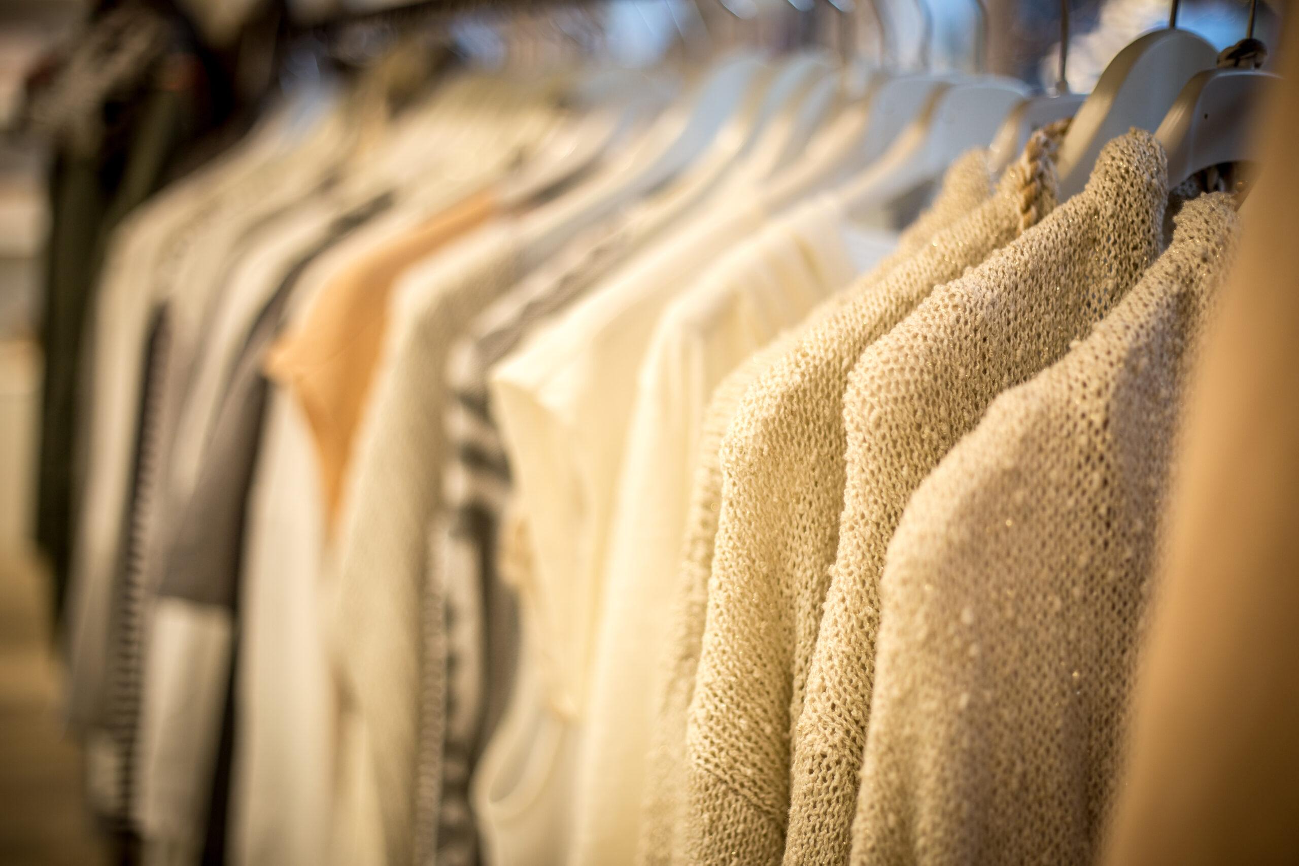 Helle Kleidung, die schön sortiert im Schaufenster an einer Kleiderstange hängt.
