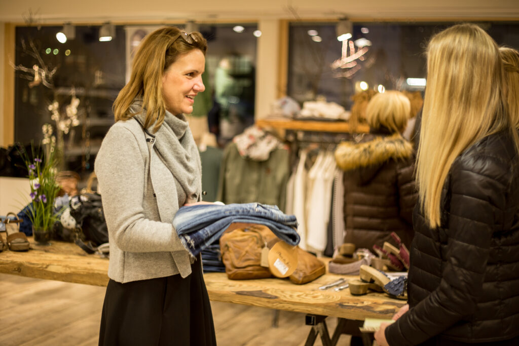 Maria Mader bedient lächelnd eine Kundin beim Prosecco-Shopping.