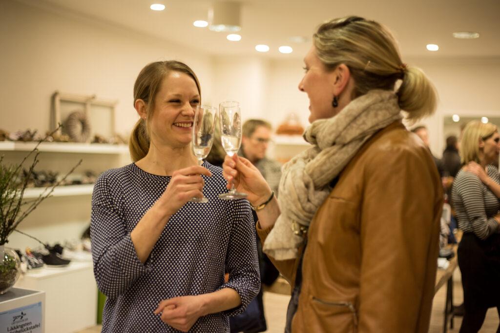 Zwei Frauen prosten sich mit Sekt beim Prosecco-Shopping im Frauenzimmer zu und lächeln dabei.